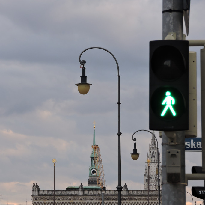 Green traffic light with skyline of Munich in the background.