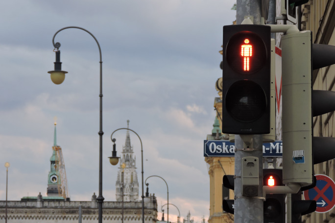Red traffic light with skyline of Munich in the background.