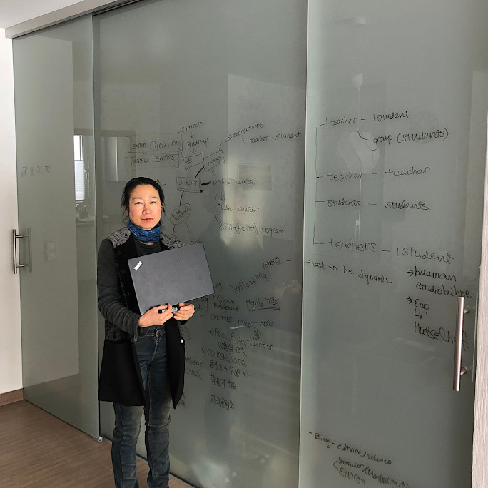 Researcher with her laptop standing in front of a sliding glass door with notes on it