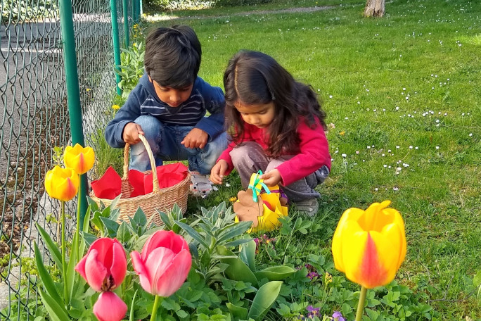 two children find easter eggs in the grass