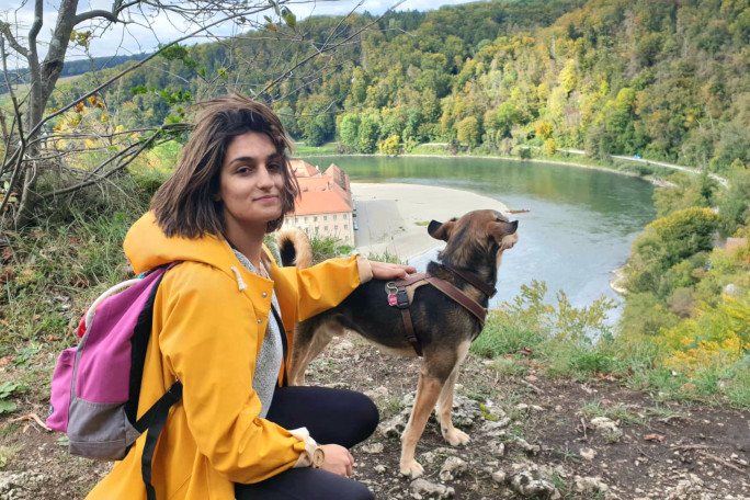 PhD student Mathilde with her dog looking at the Danube river